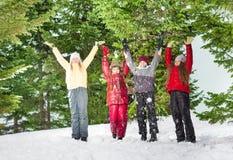 Quatre enfants se tenant dans la rangée à la forêt d'hiver Image libre de droits