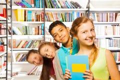 Quatre enfants se tenant dans une rangée à l'intérieur de bibliothèque Images stock
