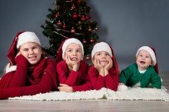 Quatre enfants sont autour d'arbre de Noël. Photographie stock libre de droits