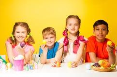 Quatre enfants tenant des oeufs de pâques à la table Photographie stock