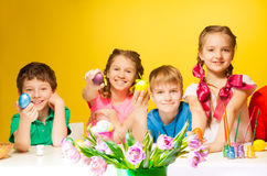 Quatre enfants tenant les oeufs de pâques colorés Photo stock