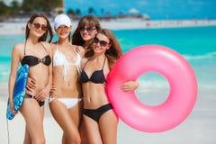 Quatre femmes dans des bikinis avec la ligne de sauvetage près de l'océan Photo stock