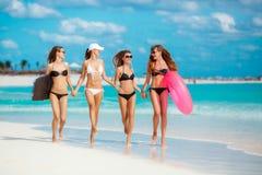 Quatre femmes dans des bikinis avec la ligne de sauvetage près de l'océan Photographie stock