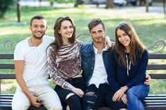 Quatre femmes et hommes s'asseyant sur le banc dans l'étreinte Photos libres de droits