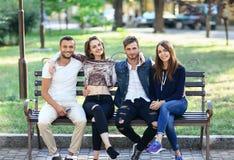Quatre femmes et hommes s'asseyant sur le banc dans l'étreinte Images stock