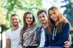 Quatre femmes et hommes s'asseyant sur le banc dans l'étreinte Photos stock