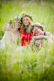 Quatre femmes portant rire de guirlandes Images stock