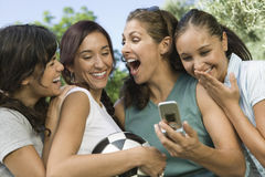 Quatre femmes riant de l'affichage de téléphone portable Image stock