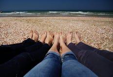 Quatre femmes se tenant sur la plage Photos stock