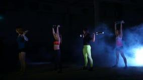Quatre femmes sexy sportives, faisant la forme physique s'exerce avec des pondérations, la nuit, dans la fumée légère, brouillard clips vidéos