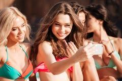 Quatre filles assez jeunes dans des bikinis faisant le selfie Images stock