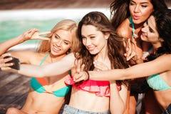 Quatre filles assez jeunes dans des bikinis faisant le selfie Image libre de droits
