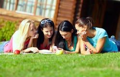 Quatre filles causent dans le réseau social sur la pelouse verte Images stock