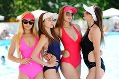 Quatre filles dans des maillots de bain sur un bassin coloré de fond Images libres de droits