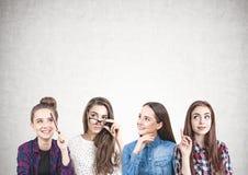 Quatre filles de l'adolescence pensant ensemble, concret Image stock