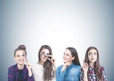Quatre filles de l'adolescence pensant ensemble, gris Photographie stock libre de droits