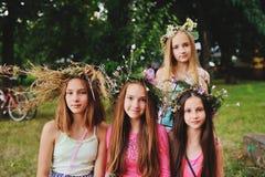 Quatre filles en guirlandes de leurs fleurs sauvages dans la perspective de nature Image stock