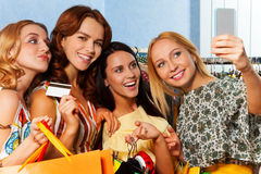 Quatre filles faisant la photo avec l'appareil-photo mobile dans la boutique Photographie stock