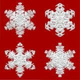 Quatre flocons de neige sur le fond rouge Image libre de droits