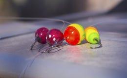 Quatre flotteurs colorés intéressants avec des crochets pour la pêche Images libres de droits