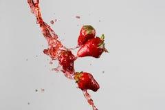 Quatre fraises et éclaboussure rouge de jus Photo stock