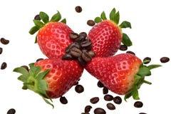 Quatre fraises mûres d'été avec les feuilles et les grains vert clair du café aromatique photographie stock libre de droits