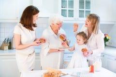 Quatre générations des femmes faisant la tarte aux pommes cuire au four Photographie stock