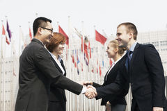 Quatre gens d'affaires de sourire rencontrant et se serrant la main dehors, Pékin photo stock