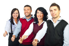 Quatre gens d'affaires donnant des pouces Images stock