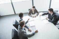 Quatre gens d'affaires s'asseyant autour d'une table et ayant une réunion d'affaires, vue courbe Photographie stock libre de droits