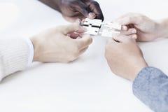 Quatre gens d'affaires tenant des morceaux de puzzle denteux et les plaçant ensemble, mains seulement Photographie stock