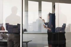Quatre gens d'affaires tenant et regardant un conseil blanc de l'autre côté d'un mur de verre Image libre de droits