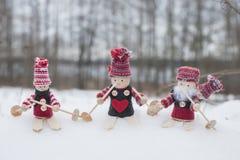 Quatre gnomes dans des chapeaux tricotés sur des skis dans le paysage neigeux dans le temps de Noël Image libre de droits