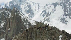 Quatre grimpeurs sur la crête de la roche La neige de observation de femme a couvert des montagnes Silhouette d'homme se recroque banque de vidéos
