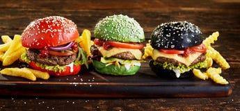 Quatre hamburgers de boeuf sur les petits pains colorés image stock