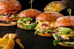 Quatre hamburgers faits maison sur la table en bois Petits pains avec les graines de sésame, des hamburgers de boeuf et de divers images stock