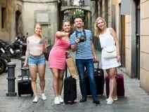 Quatre heureuses personnes de déplacement marchant dans la ville Photos stock