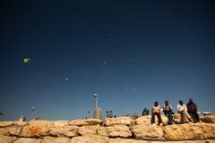 Quatre hommes apprécient l'été sur le mur de briques près de la plage Images libres de droits
