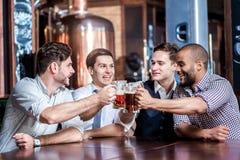Quatre hommes d'affaires boivent de la bière et se réjouissent ensemble à la barre Suc Images stock