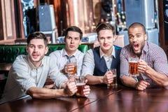 Quatre hommes d'affaires boivent de la bière et se réjouissent et crient ensemble montre Image libre de droits