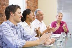 Quatre hommes d'affaires dans des applaudissements de salle de réunion Image stock