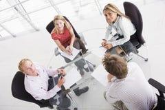 Quatre hommes d'affaires dans la salle de réunion avec des écritures Photo stock