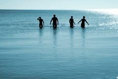 Quatre hommes dans l'eau Photo stock