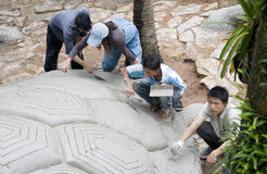 Quatre hommes ont effectué la sculpture en tortue Photographie stock