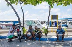Quatre hommes s'asseyant sur le trottoir au secteur de docks Photographie stock libre de droits