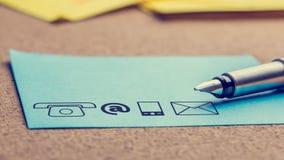 Quatre icônes de contact imprimées sur un papier bleu-clair Images stock