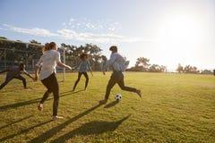 Quatre jeunes adultes jouant le football en parc au coucher du soleil Photographie stock