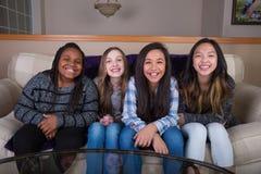 Quatre jeunes amies s'asseyant sur un divan à la maison Photos stock