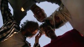 Quatre jeunes amis étreignant le regard vers le bas sur la terre posant le jour ensoleillé Jeunesse élégante, amitié heureuse tra banque de vidéos