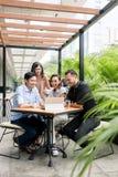 Quatre jeunes amis asiatiques observant ensemble le contenu en ligne drôle Photo stock
